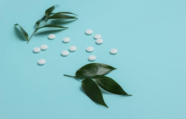 Comprimidos de ervas comprimidos brancos com folhas verdes em um fundo azul pastel