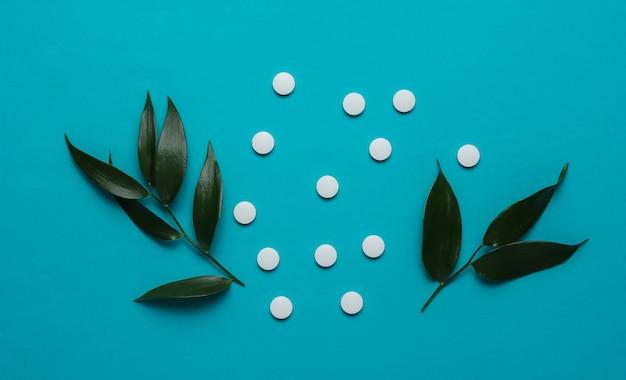 Comprimidos de ervas comprimidos brancos com folhas verdes sobre fundo azul