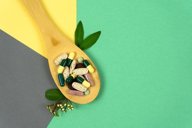 Comprimidos de ervas em uma colher de pau com ervas em fundos coloridos vitaminas de medicina alternativa