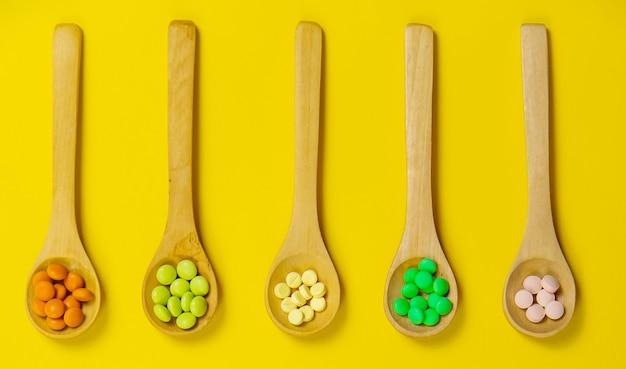 Comprimidos de ervas mistos em uma colher de pau. suplemento alimentar. foco seletivo