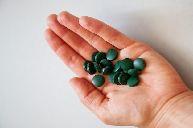 Comprimidos de espirulina verde na palma da mão de um humano.