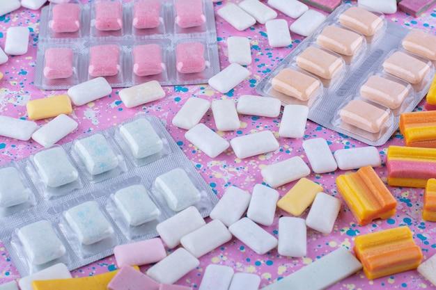 Comprimidos de goma em meio a pedaços de chiclete espalhados em uma superfície colorida