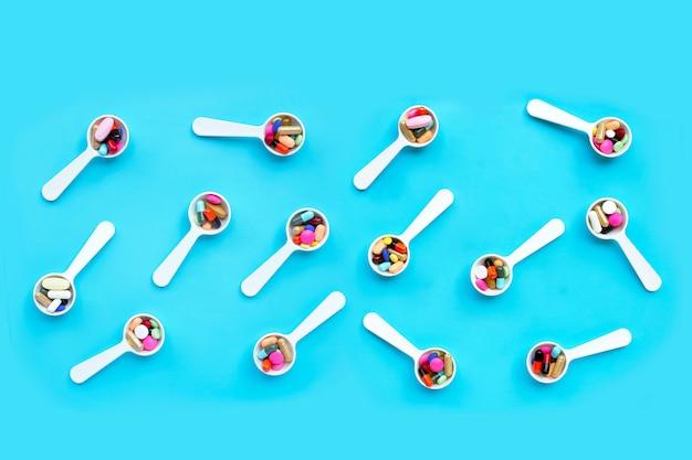 Comprimidos de medicamento colorido, comprimidos e cápsulas em fundo azul