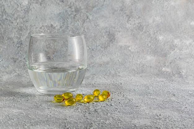 Comprimidos de medicamento e copo de água em cinza. conceito de medicina de tratamento de doenças respiratórias. prevenção de propagação de doenças