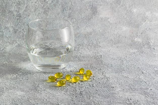Comprimidos de medicamento e copo de água no fundo cinza. conceito de medicina de tratamento de doenças respiratórias. prevenção de propagação de doenças