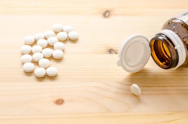 Comprimidos de medicamento em fundo de madeira