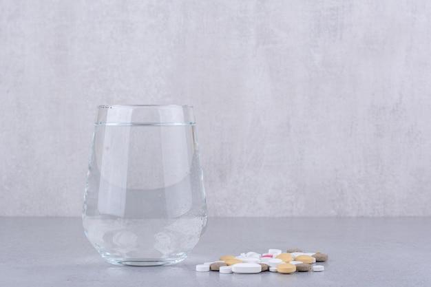 Comprimidos de medicamento farmacêutico sortidos e copo de água. foto de alta qualidade