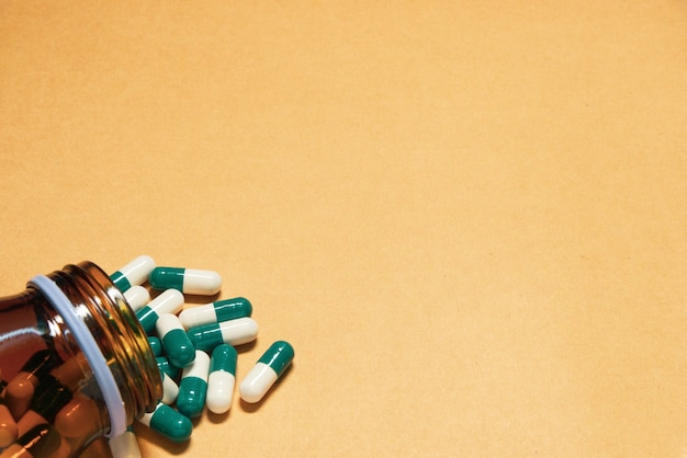 Comprimidos de medicamentos caindo de um frasco de vidro em um fundo laranja claro com espaço de cópia