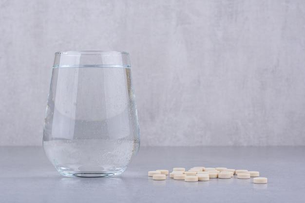 Comprimidos de medicamentos farmacêuticos e copo de água. foto de alta qualidade