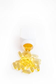 Comprimidos de ômega 3 saindo do frasco em um fundo branco