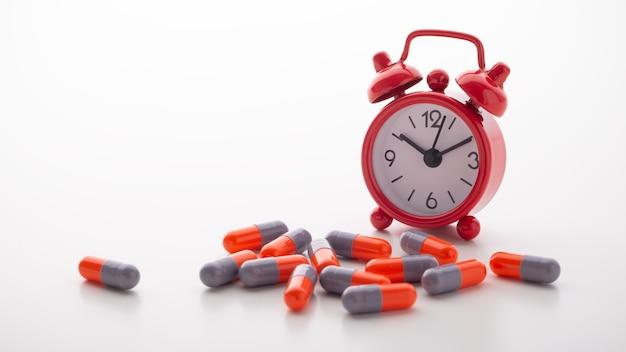 Comprimidos de remédio com despertador vermelho