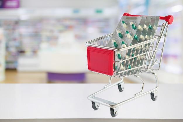Comprimidos de remédio em cápsula de blister no carrinho de compras no balcão da farmácia com desfocar o fundo desfocado das prateleiras das drogarias
