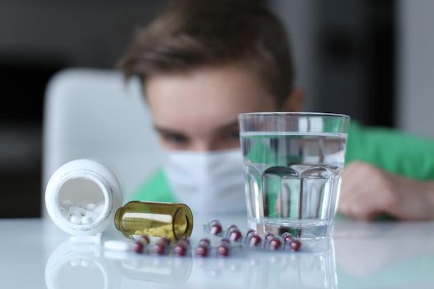 Comprimidos de um resfriado em uma mesa branca e chateado menino. stop virus