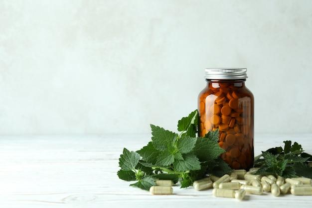 Comprimidos de urtiga e ingredientes na mesa de madeira branca