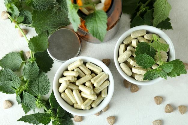 Comprimidos de urtiga e ingredientes na mesa texturizada branca
