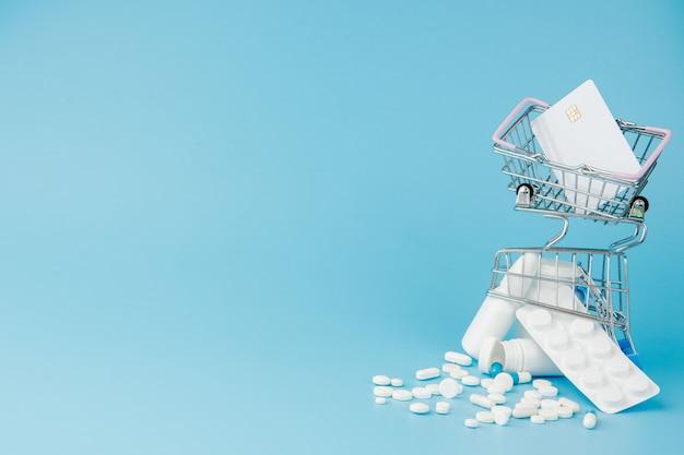 Comprimidos de variedade espalhada, drogas, spay, garrafas, termômetro, seringa e carrinho de carrinho de compras vazio sobre fundo azul. conceito de compras de farmácia.