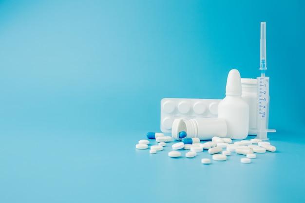 Comprimidos de variedade espalhada, drogas, spay, garrafas, termômetro, seringa e carrinho de compras vazio sobre fundo azul. conceito de compras de farmácia.
