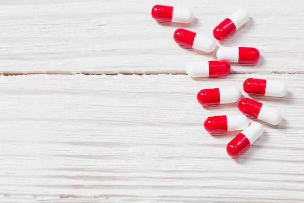Comprimidos de vermelhos e brancos em fundo de madeira