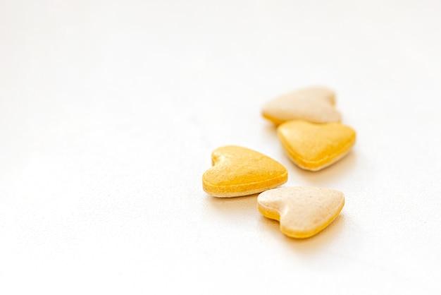 Comprimidos de vitamina amarelos em forma de coração na superfície branca