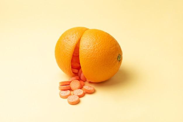 Comprimidos de vitamina c caindo de duas metades da casca de laranja, em um amarelo