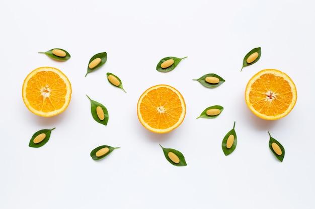 Comprimidos de vitamina c com fruta laranja em branco