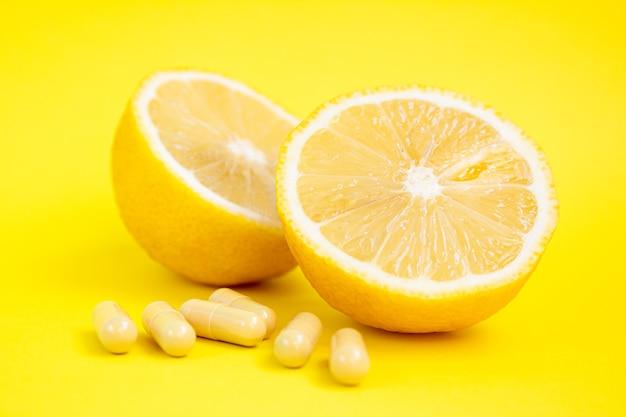 Comprimidos de vitamina c em cápsulas de vitamina c e limão amarelo sobre fundo amarelo