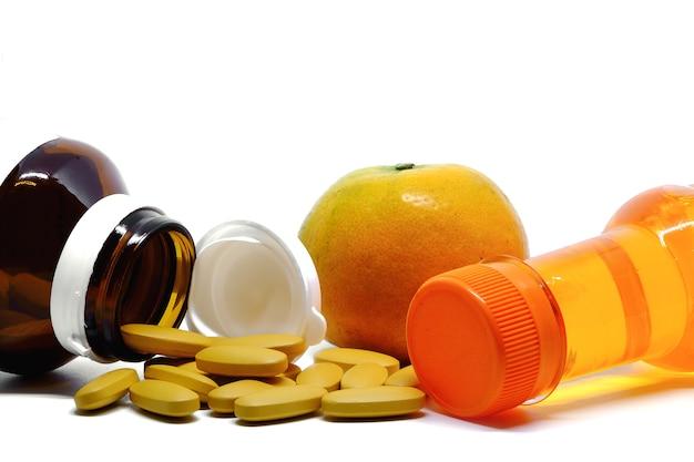 Comprimidos de vitamina c, frutas frescas de laranja e garrafa de bebida doce