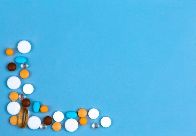 Comprimidos definidos como fronteira. os comprimidos coloridos ajustaram-se como a beira no fundo azul com espaço da cópia para o texto.