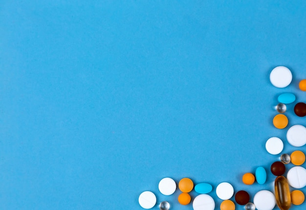 Comprimidos definidos como fronteira. pílulas coloridas definidas como fronteira em fundo azul