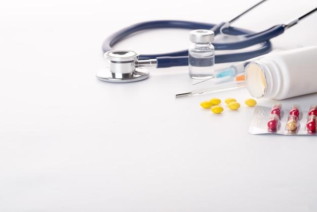 Comprimidos derramando do termômetro da seringa do frasco de comprimidos e do estetoscópio no fundo branco