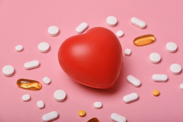 Comprimidos diferentes e coração vermelho isolado em rosa