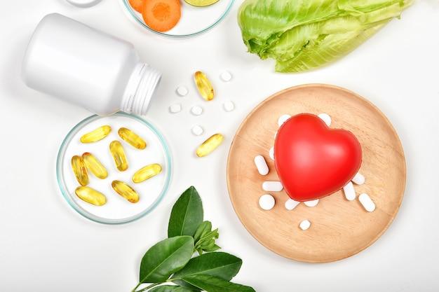 Comprimidos diferentes e coração vermelho isolado no branco