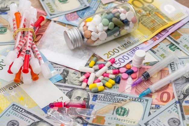 Comprimidos diferentes em notas de dólar e euro.