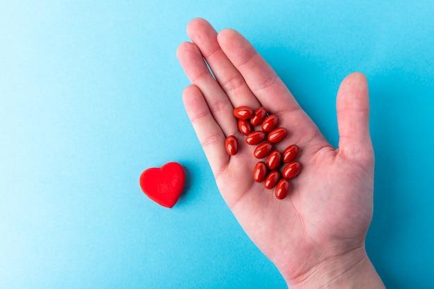 Comprimidos do frasco e coração vermelho no azul
