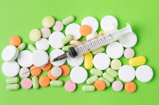 Comprimidos, drogas e antibióticos das medicinas em um fundo verde. medicina e cuidados de saúde.