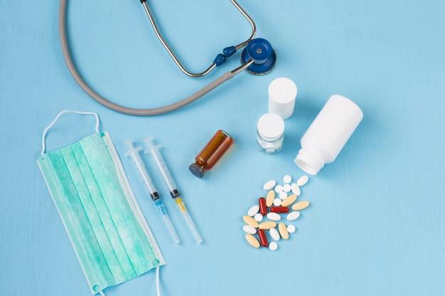 Comprimidos, duas seringas, um estetoscópio e uma máscara
