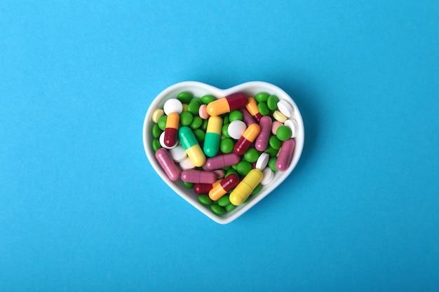 Comprimidos e cápsulas coloridos da variedade na placa.