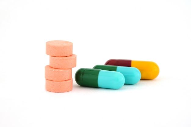 Comprimidos e cápsulas isoladas no fundo branco