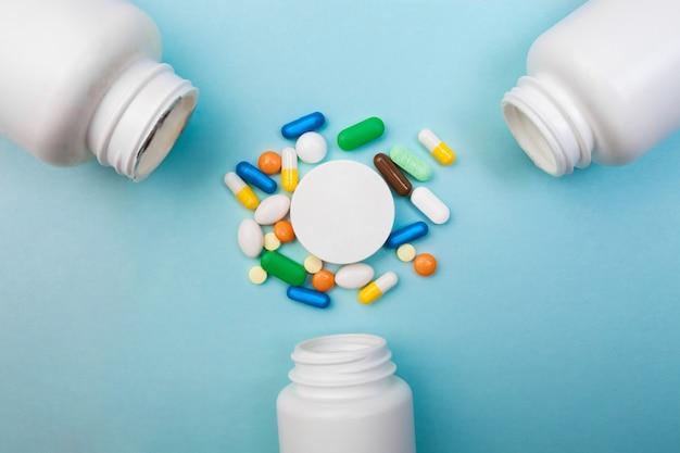 Comprimidos e cápsulas multicoloridas e frascos brancos para comprimidos