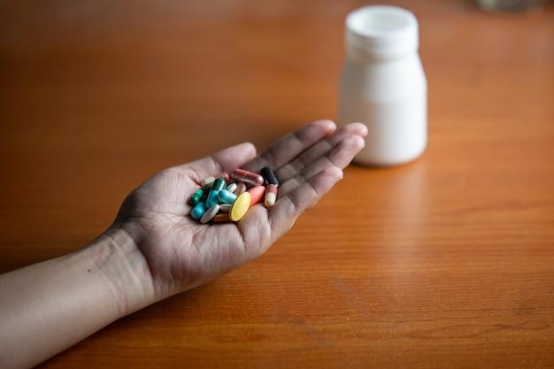 Comprimidos e cápsulas na mão das mulheres