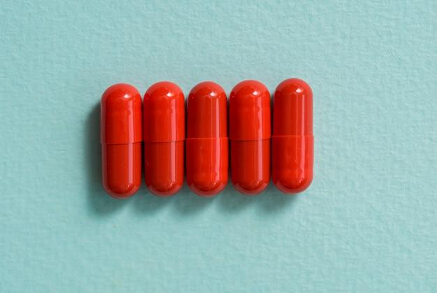 Comprimidos e cápsulas vermelhos em um fundo azul. cápsula aberta, medicamento em pó