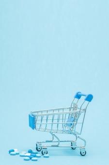 Comprimidos e carrinho de compras em azul
