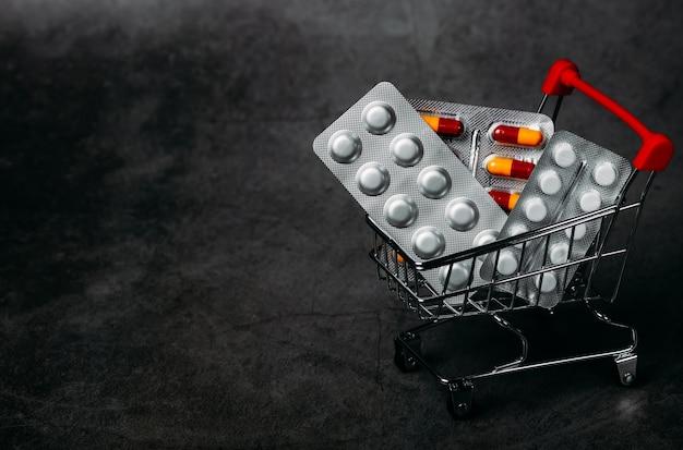 Comprimidos e carrinho de compras no conceito de economia de fundo escuro. saúde e medicina