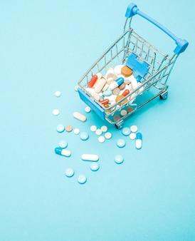 Comprimidos e carrinho de compras sobre fundo azul