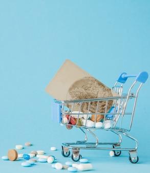 Comprimidos e cartão de crédito no carrinho de compras em fundo azul