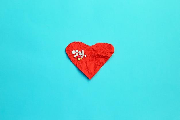 Comprimidos e coração de papel amarrotado vermelho no fundo azul.