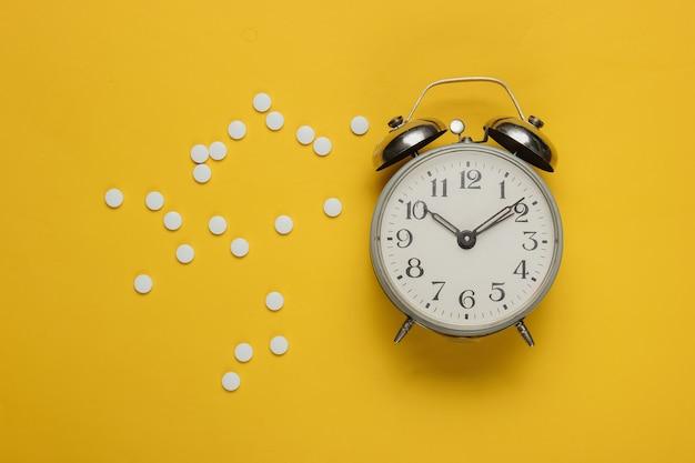 Comprimidos e despertador em amarelo