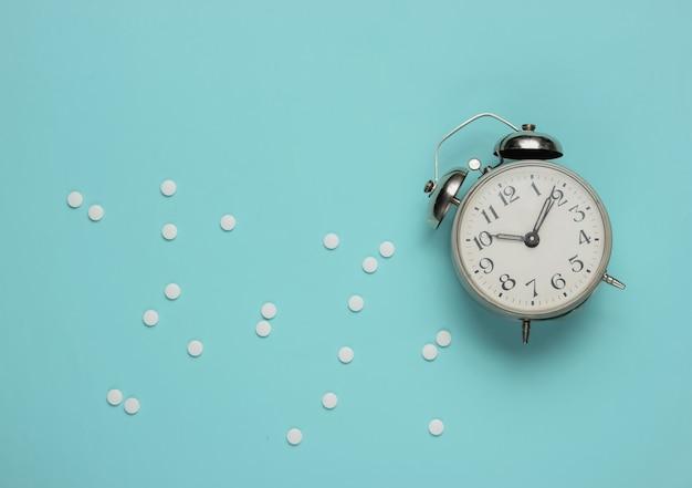 Comprimidos e despertador em azul