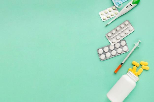 Comprimidos e ferramentas médicas sobre a superfície verde com espaço para texto