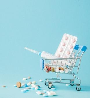 Comprimidos e injeção médica em carrinho de compras sobre fundo azul